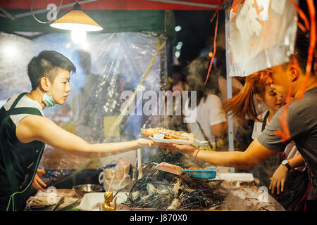 CHIANG MAI, THAILAND - AUGUST 27: Food vendor cooks and sells fish and seafood at the Saturday Night Market (Walking - Stock Photo