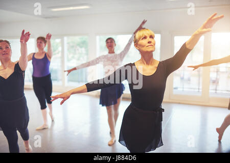 Group of adult ballerinas standing with hands up in class for ballet performing a dance. - Stock Photo