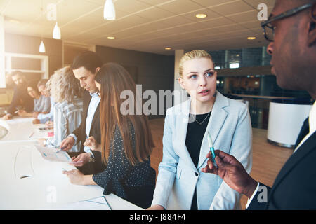 Black and white men and women working in modern office discussing and planning work during the conference. - Stock Photo