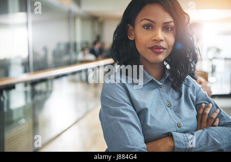 Pretty young dreamy African-American office worker standing with arms crossed and looking at camera. - Stock Photo
