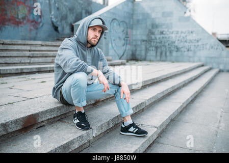 Dance performer sitting on the steps, urban dancing style, street dancing. Male dancer - Stock Photo