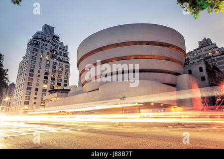 Goggenheim museum at night in New York City with traffic lights in front - Stock Photo