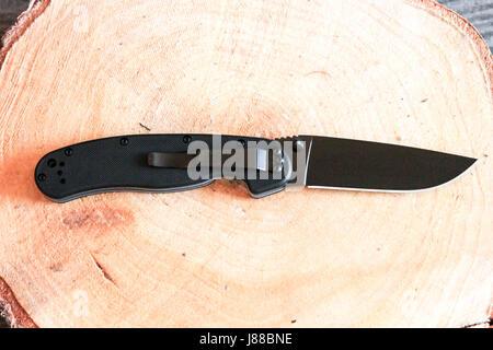 Pocket knife in unfolded form with a pocket clip. Black knife. - Stock Photo
