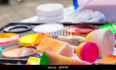 Color cosmetics, brushes and sponges for face painting. Children party - Stock Photo