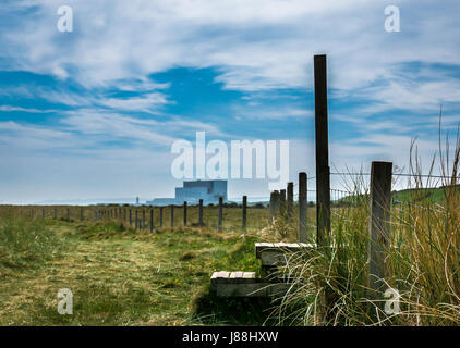 Ground level view along John Muir Way coastal path, with Torness Nuclear Power Station on horizon and stile over - Stock Photo