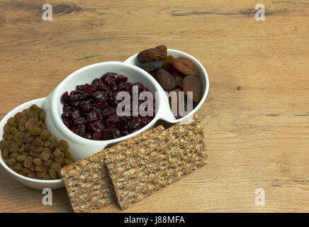 Dried apricots, cranberries, raisins and two pieces of crisp bread on an old,wooden, kitchen table. Close, horizontal - Stock Photo