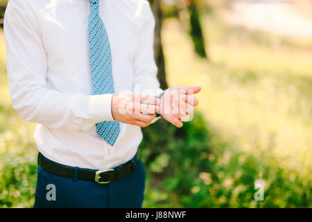 A man in a shirt and tie, puts his hand on the clock. Wedding groom accessories. - Stock Photo