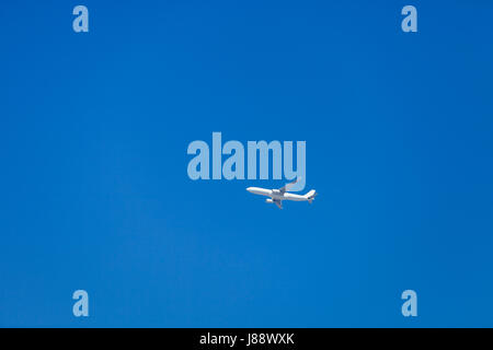 Aeroplane flying in the blue sky. - Stock Photo
