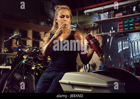 Woman mechanic lights up a cigarette with a gas burner in a motorcycle workshop - Stock Photo