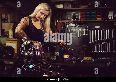 Blond woman mechanic working in a motorcycle workshop - Stock Photo