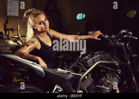 Blond woman mechanic in a motorcycle workshop - Stock Photo