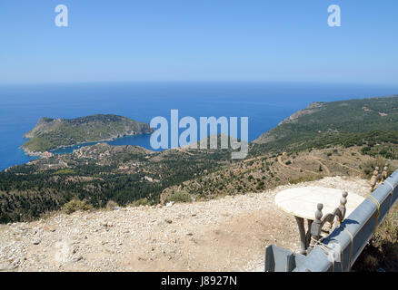 Chairs and table on the road  to Assos  village with panoramic view of Assos peninsula in Kefalonia , Greece - Stock Photo