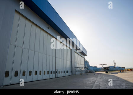 Airport hangar from the outside with big tall doors. Bright blue sky. - Stock Photo