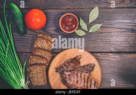 Pieces of grilled veal, brown wooden background, vintage toning - Stock Photo