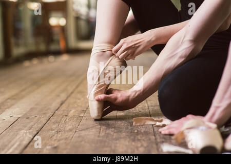 Young ballerina or dancer girl putting on her ballet shoes on the wooden floor. Male ballet dancer helps puttiing - Stock Photo