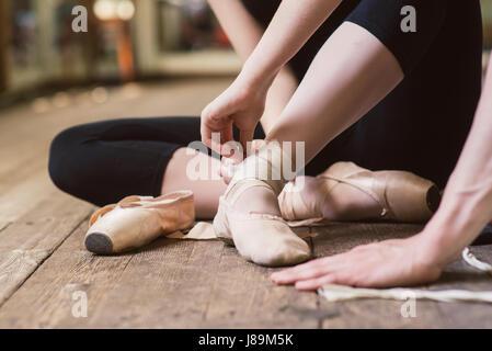 Young ballerina or dancer girl putting on her ballet shoes on the wooden floor. Ballet dancer tying ballet shoes. - Stock Photo