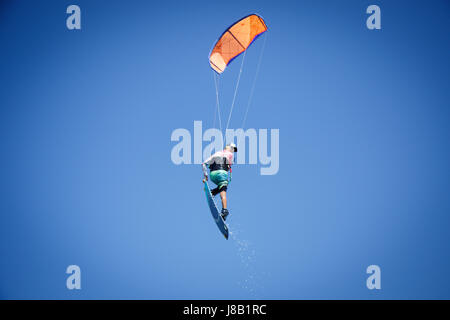 Professional kite boarding rider sportsman with kite in sky jumps high acrobatics kiteboarding trick with grab of - Stock Photo