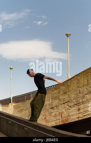 A young man is jumping from a high wall. Parkour in the urban space. Sport in the city. Sport Activities outdoors. - Stock Photo
