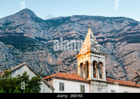 Medieval Bell Tower and Biokovo Mountains in the Background, Makarska, Croatia - Stock Photo