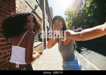 Shot from behind of two young women walking on city street. Female friends walking together outdoors and having - Stock Photo