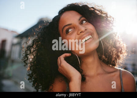 Close up portrait of young african woman with curly hair looking away. Afro american female standing outdoors and - Stock Photo