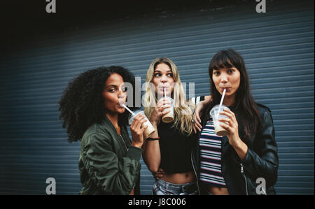 Beautiful young females having ice coffee outdoors. Multiracial group of women friends drinking coffee. - Stock Photo