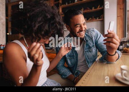 Smiling young couple sitting at coffee shop using mobile phone. Young man and woman at cafe taking selfie and laughing. - Stock Photo