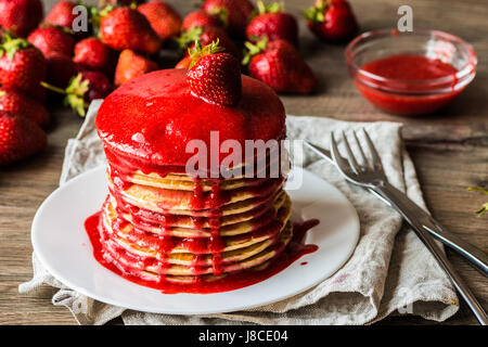 Macro american pancakes with strawberry jam on a wooden background. Shallow depth of field. - Stock Photo