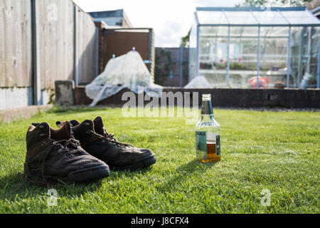 A pair of water soaked brown boots next to an open bottle of beer on a hot sunny day. After a hard day's work in - Stock Photo