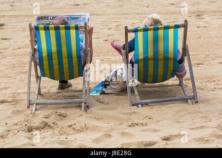 Bournemouth, Dorset, UK. 28th May, 2017. UK weather: overcast day at Bournemouth beaches, but the sun is trying to break through. Visitors head to the seaside to make the most of the Bank Holiday weekend. Couple in deckchairs on Bournemouth beach.  Credit: Carolyn Jenkins/Alamy Live News