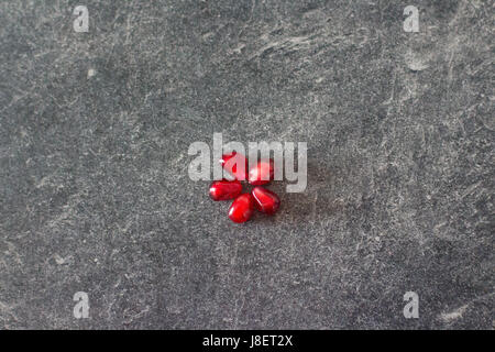 pomegranate seeds on gray background - Stock Photo