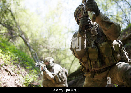 Officers on military mission in woods during day - Stock Photo