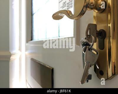 Bunch of keys in front door lock - Stock Photo