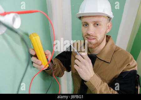 builder using a yellow multimeter to calibrate house - Stock Photo