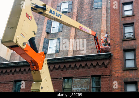 Two men restoring the wall of an old building in Soho, New York City, working from the platform of a JLG Telescopic - Stock Photo