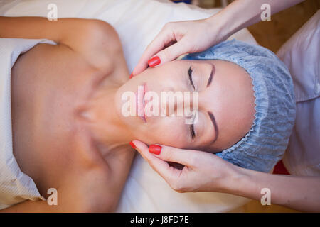 doctor cosmetologist doing facial massage girl spa - Stock Photo