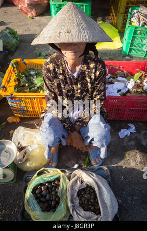Nha Trang, Vietnam - December 02, 2015: Senior Vietnamese woman in traditional hat is selling snails at the street - Stock Photo