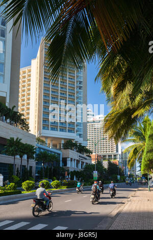 Nha Trang, Vietnam - December 09, 2015: Local people riding a motorbike in front of the luxury hotels on the seafront - Stock Photo