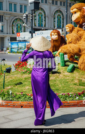 Ho Chi Minh City, Vietnam - February 07, 2016: Vietnamese woman in traditional Ao Dai dress poses for picture at - Stock Photo