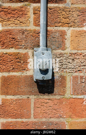 Industrial electric light switch on a bare brick wall - Stock Photo