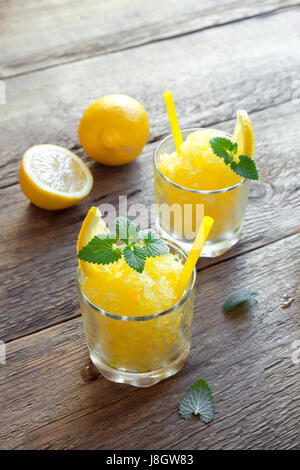 Lemon Frozen Granita Slush Drink in glasses on rustic wooden table. Homemade Italian Granita Dessert, refreshing - Stock Photo
