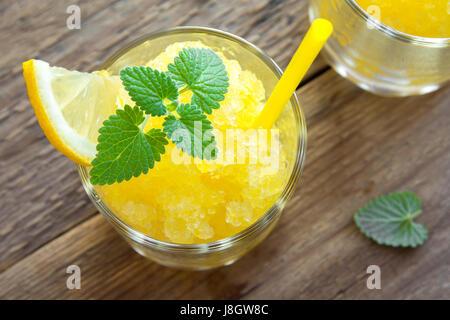Lemon Frozen Granita Slush Drink in glasses on rustic wooden table. Homemade Italian Granita Dessert, refreshing - Stock Photo