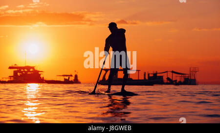 Active paddle boarder. Black sunset silhouette of young sportsman paddling on stand up paddleboard. Healthy lifestyle. - Stock Photo