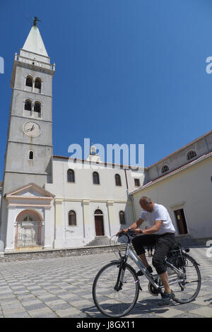 A man cycling a long the church in Croatia - Stock Photo