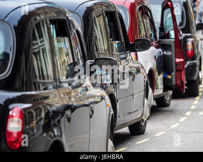 London Taxis Black Cabs queue for passengers at a Central London Railway Station - Stock Photo