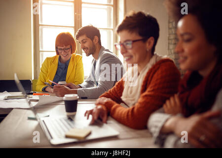 young couple designers looking at color swatches in hands - Stock Photo