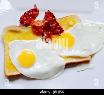 Bacon and fried eggs on white toast - Stock Photo