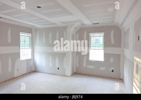 new home under construction - the sheetrock is up and mudded - Stock Photo