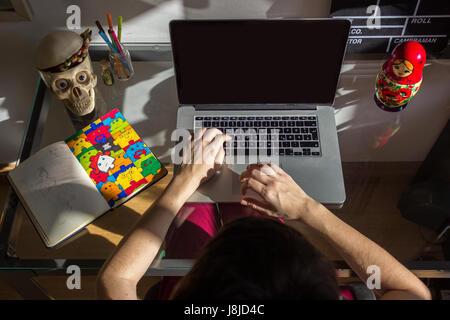 Brazil, Rio de Janeiro - May 27, 2016: Young creative working on computer - Stock Photo