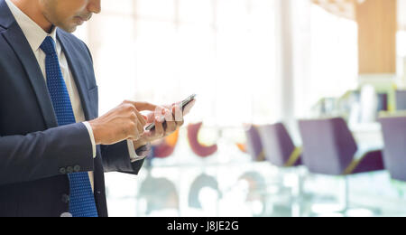 Businessman using mobile phone with blur bank office background with bokeh light. - Stock Photo